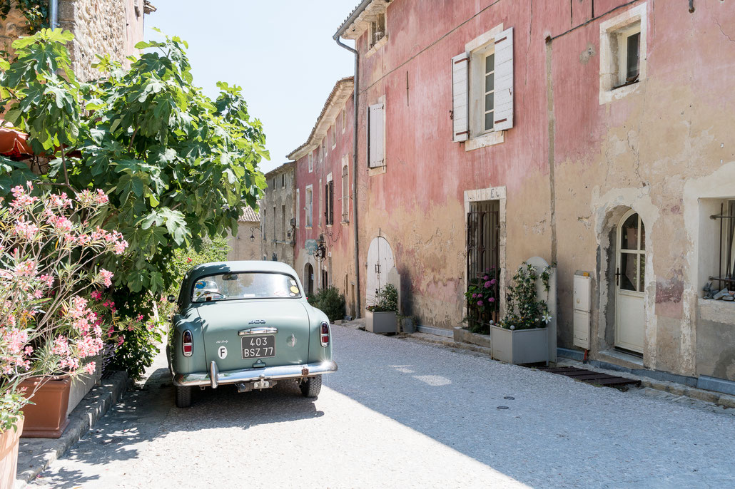 It can't get more provencal then this: A classic french car along with plants and flowers opposite a washed out red wall