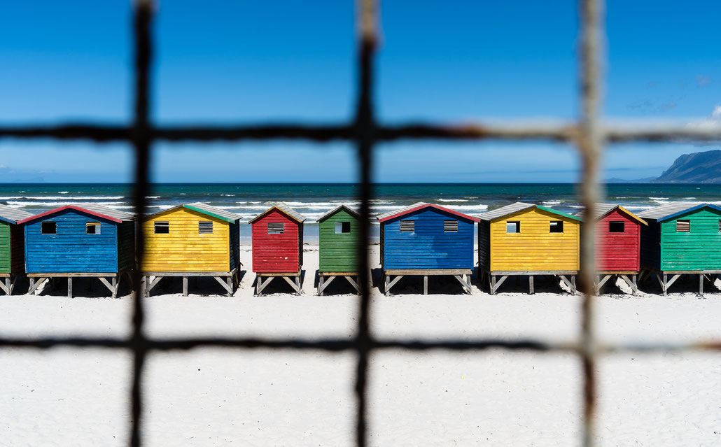 Colourful beach houses of Muizenberg, South Africa, through a fence