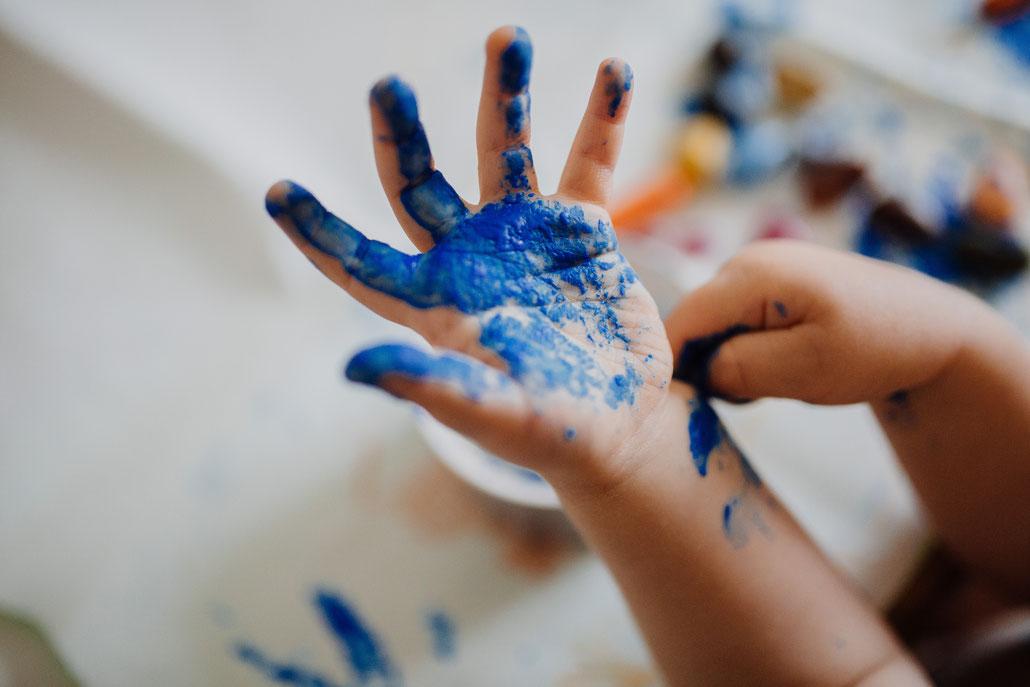 Bild von Kinderhand mit blauer Farbe