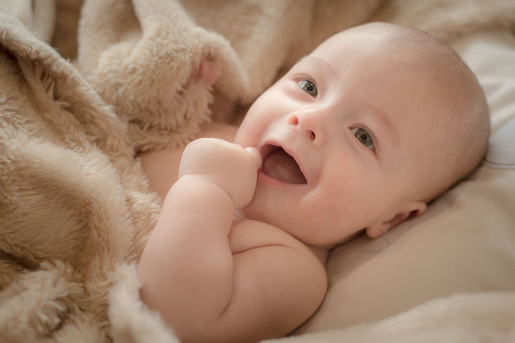 Se trata de una foto tomada por zunzu de un precioso recién nacido que se encuentra agarrando una manta.