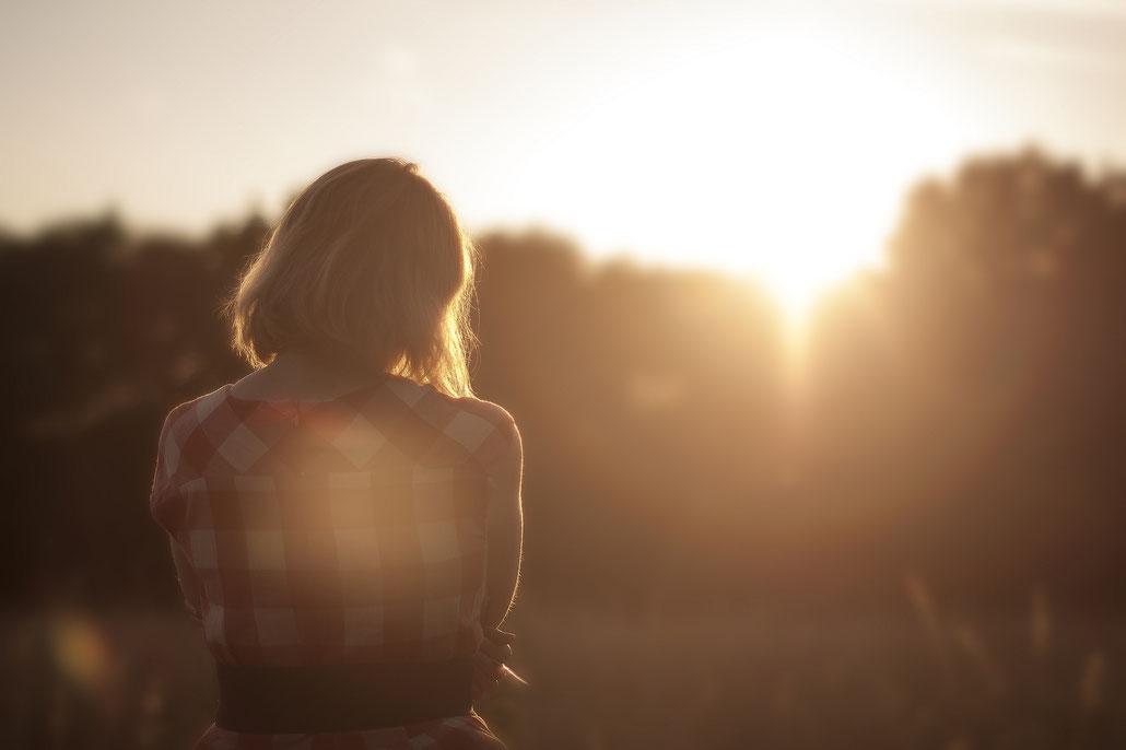 Mujer mirando a la puesta de sol