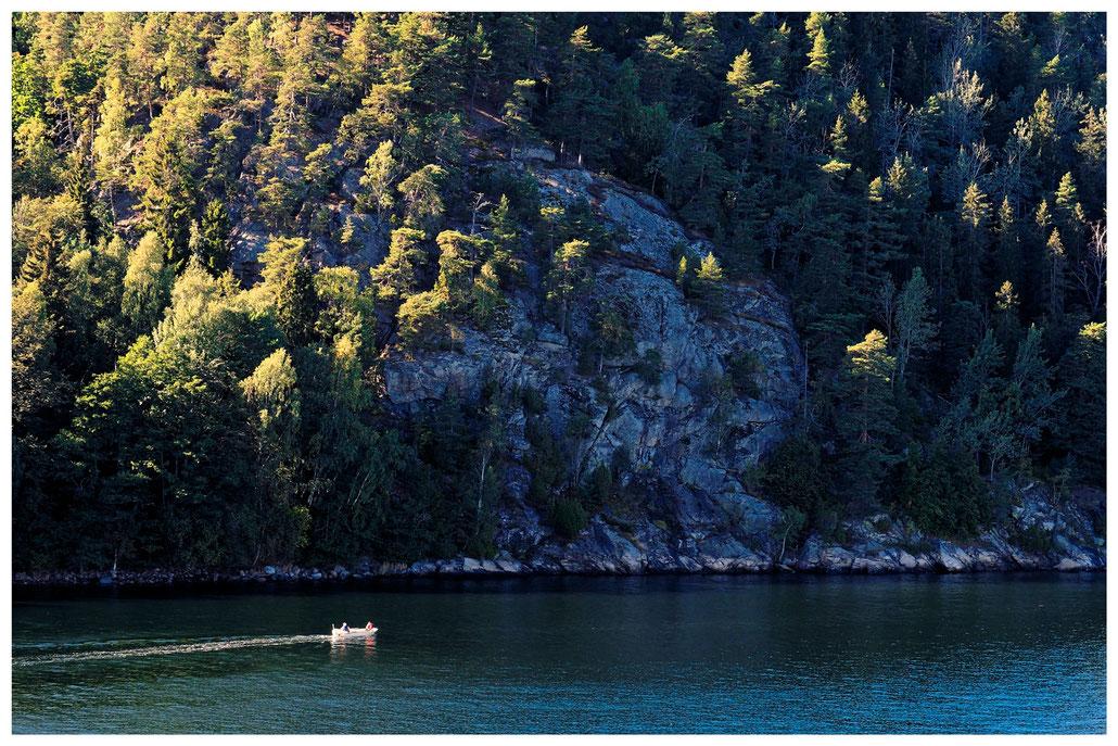 kleines Motorboot vor Felsen und Kiefern im Oslofjord