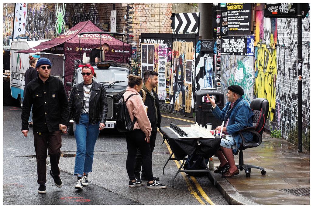 Schachspieler wartet auf Kundschaft in der Brick Lane in London