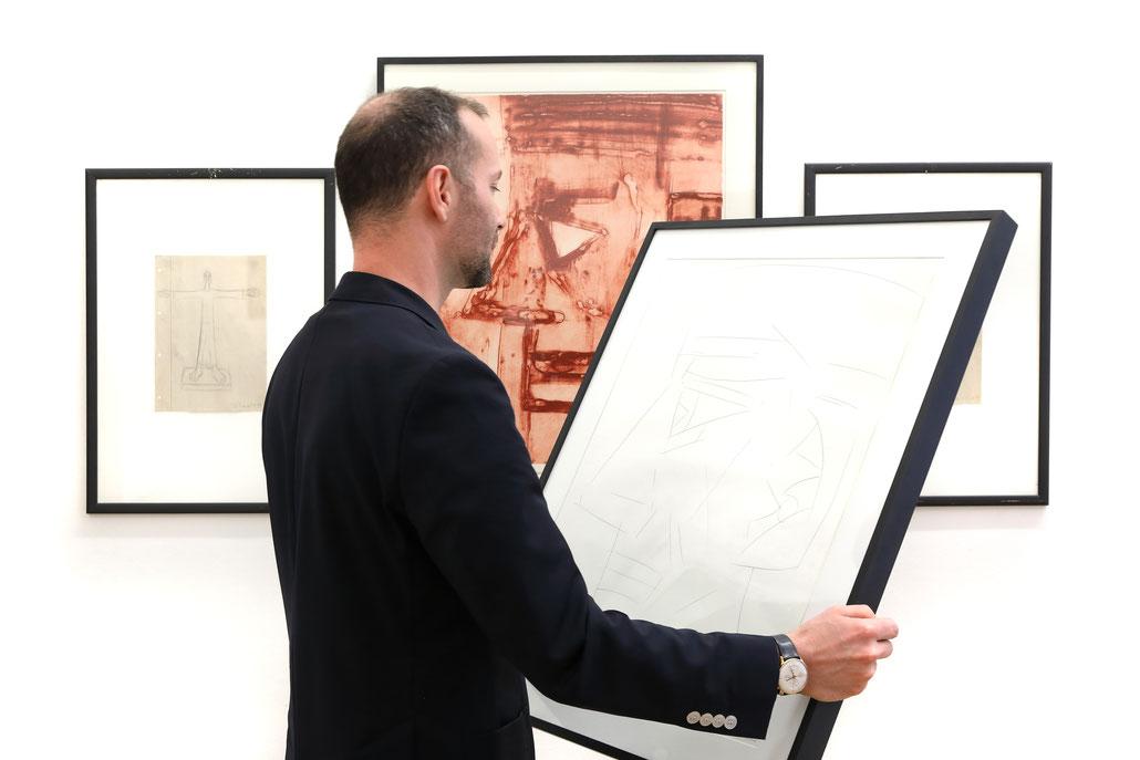 Hubert Schmalix Bilder kaufen im Kunst online Shop. Matthias Bechtle hält eine Original Zeichnung von Hubert Schmalix.