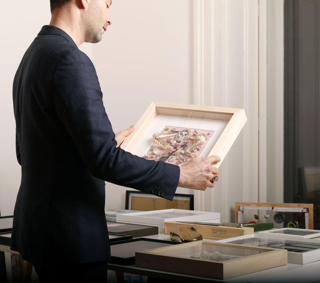 Matthias Bechtle holding an artwork by Daniel Spoerri