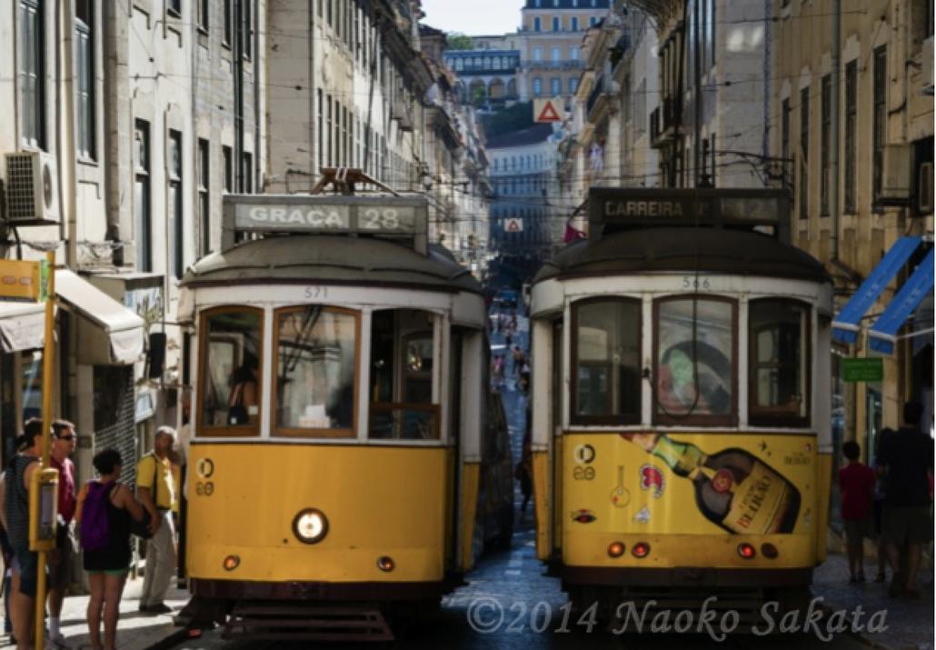 写真01 : 起伏の豊かな道をぎりぎりすれ違いながら走り抜ける、リスボン市内のトラム