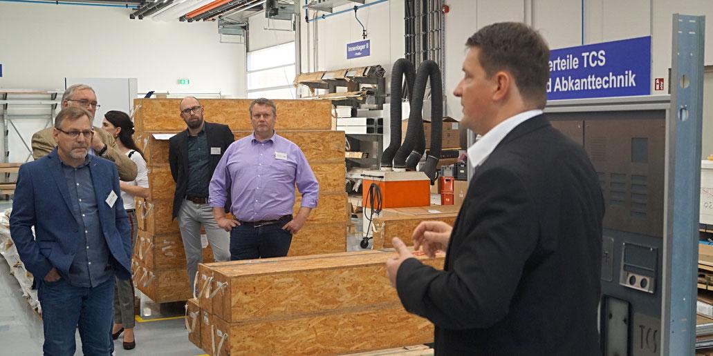 TCS-Produktmanager Ralf Usnerus zeigt seinen Besuchern die Fertigungshallen des Genthiner Unternehmens. Foto: Alpha-Report