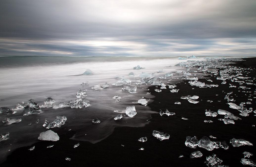 Little ice rocks looking like diamonds at the black sand at diamond beach close to Jokulsarlon, Atlantic Ocean, Iceland