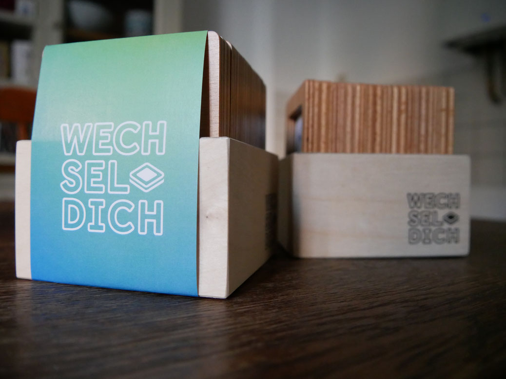 Zwei Wechsel-Dich mit den magnetischen und nachhaltigen Holzrahmen. Die Banderole zeigt das Logo des Wechsel-Dich. Auf der Seite ist das Logo des Wechsel-Dich aufgedruckt.