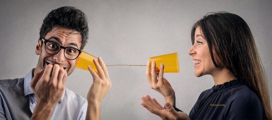 Frau spricht mit Mann am Dosentelefon, Sie lächelt, Er ist überrascht