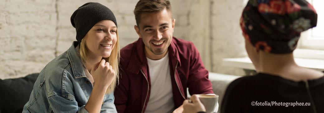 zwei Menschen lächeln und eine Frau hört zu