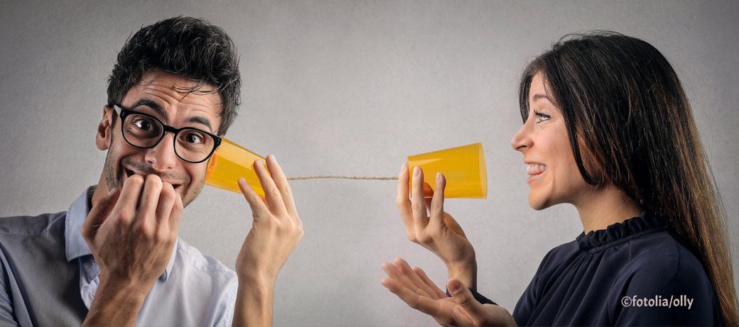 Frau kommuniziert mit Mann. Er hört zu und ist überrascht.