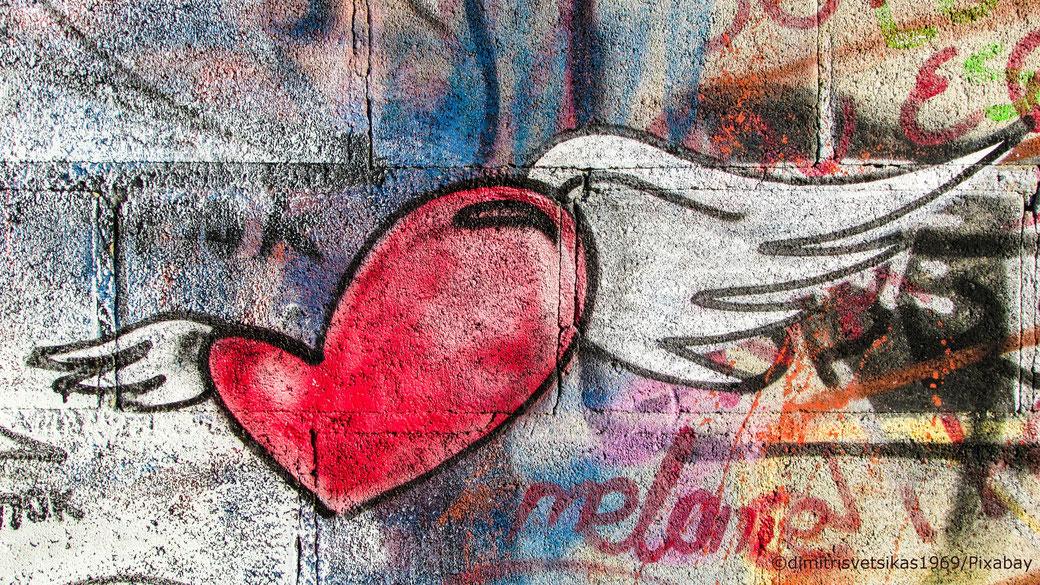 ein Herz mit Flügeln an einer Graffiti Wand