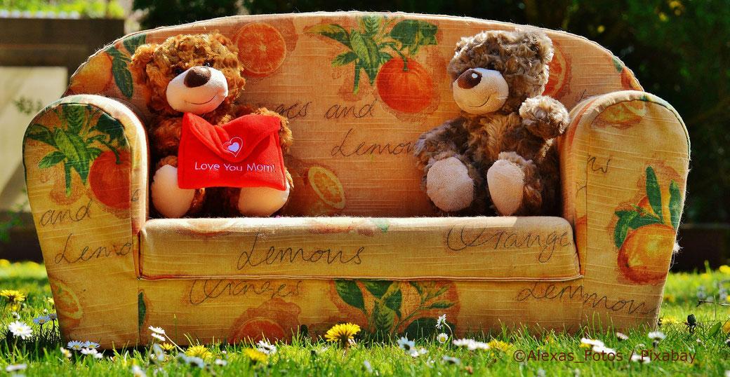 zwei Teddys sitzen auf einem bunten Sofa in der Wiese und haben sich lieb