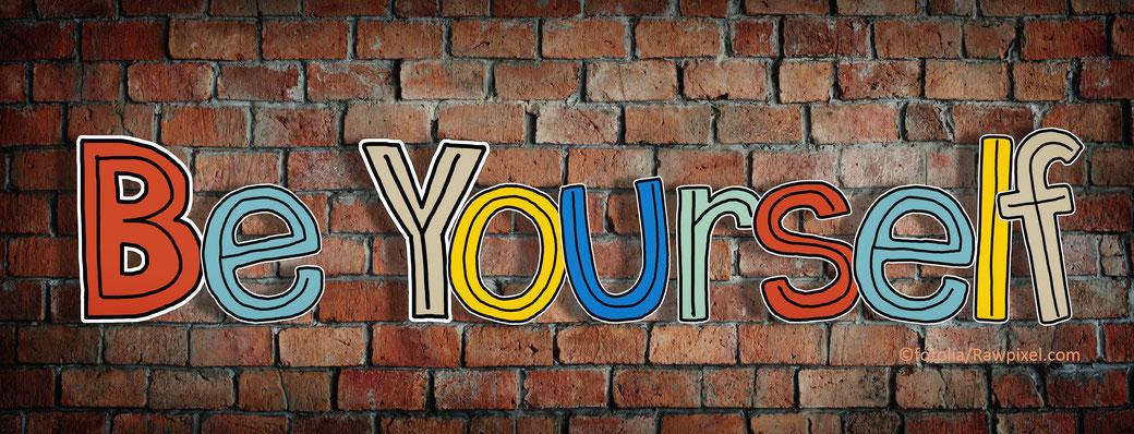 vor einer roten Backsteinwand stehen bunt die Buchstaben: Be Yourself - Sie du selbst