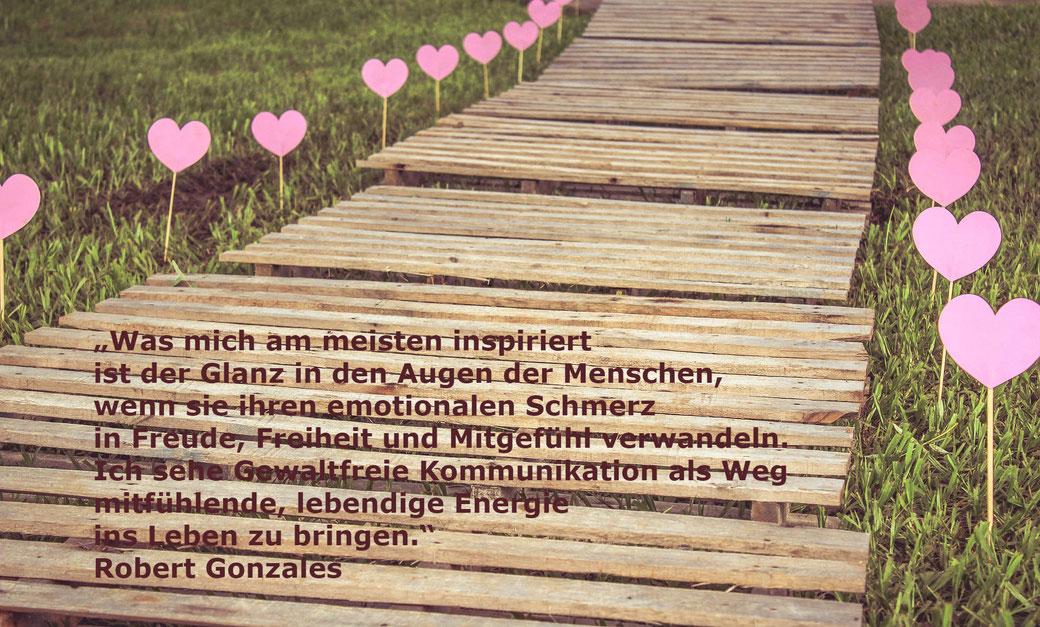 Spruch steht auf einer hölzernen Brücke, die mit rosa Herzen gesäumt ist