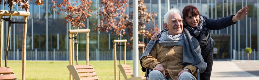 Frau spricht voll Wertschätzung mit altem Mann vor einem Seniorenheim