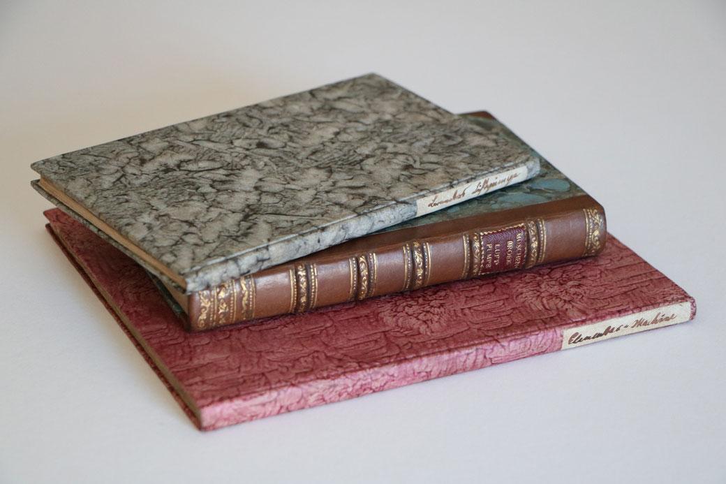 Drei fertige Bucheinbände im Stil der Zeit. Pappband mit handgemachten Kleisterpapieren und handgeschriebenen Titelschildern. Halblederband mit Mamorpapier und geprägtem Blattgold Rückendekor.