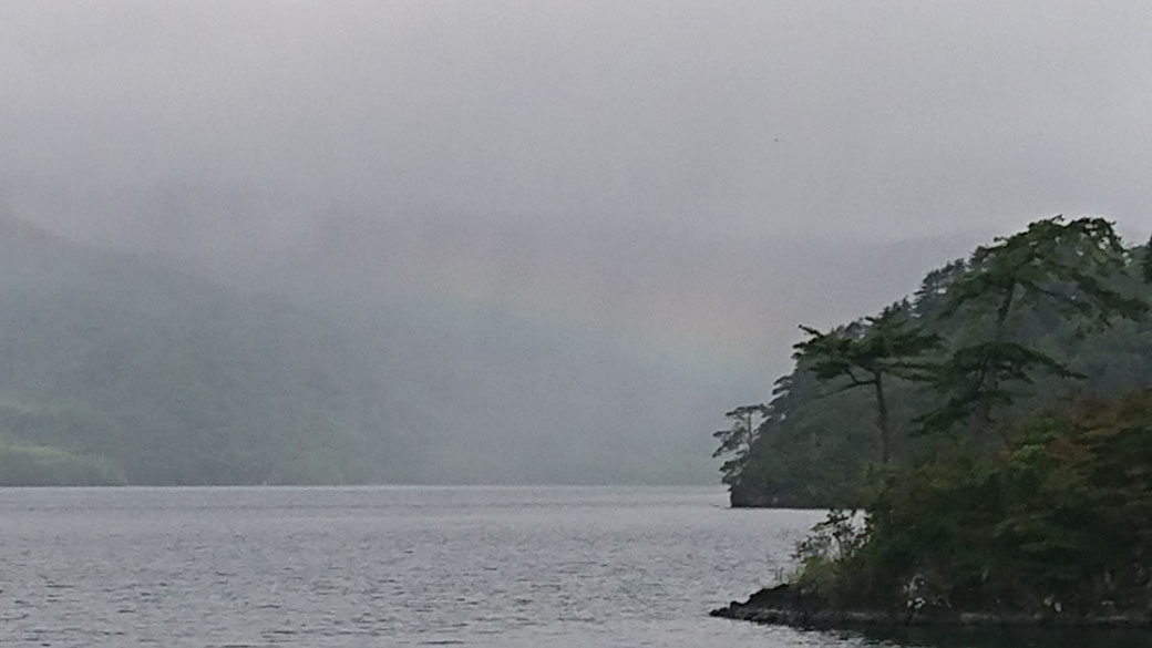 The rainbow of TOWADAKO. View from the YASUMIYA village. The view seen from YASUMIYA village is only one sixth of the whole lake. I want you to see the whole Towadako. That is another reason to recommend a canoe or motorboat.