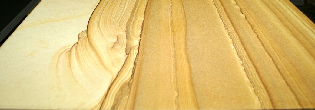 Gamtos sukurti smiltainio raštai virtuvės stalviršio plokštėje