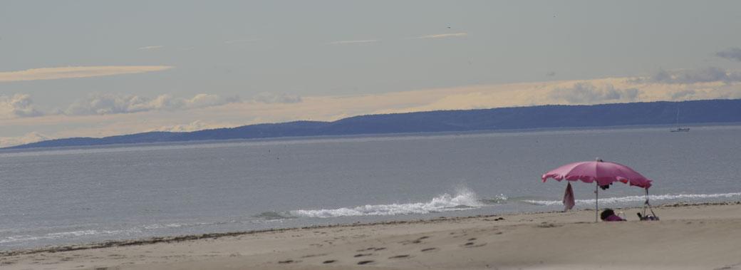 Bord de plage avec traces de pas bien visibles, , mer calme bleu grisâtre, petite vague avec écume blanche  devant un parasol rose sur lequel plusieurs objets sont suspendus