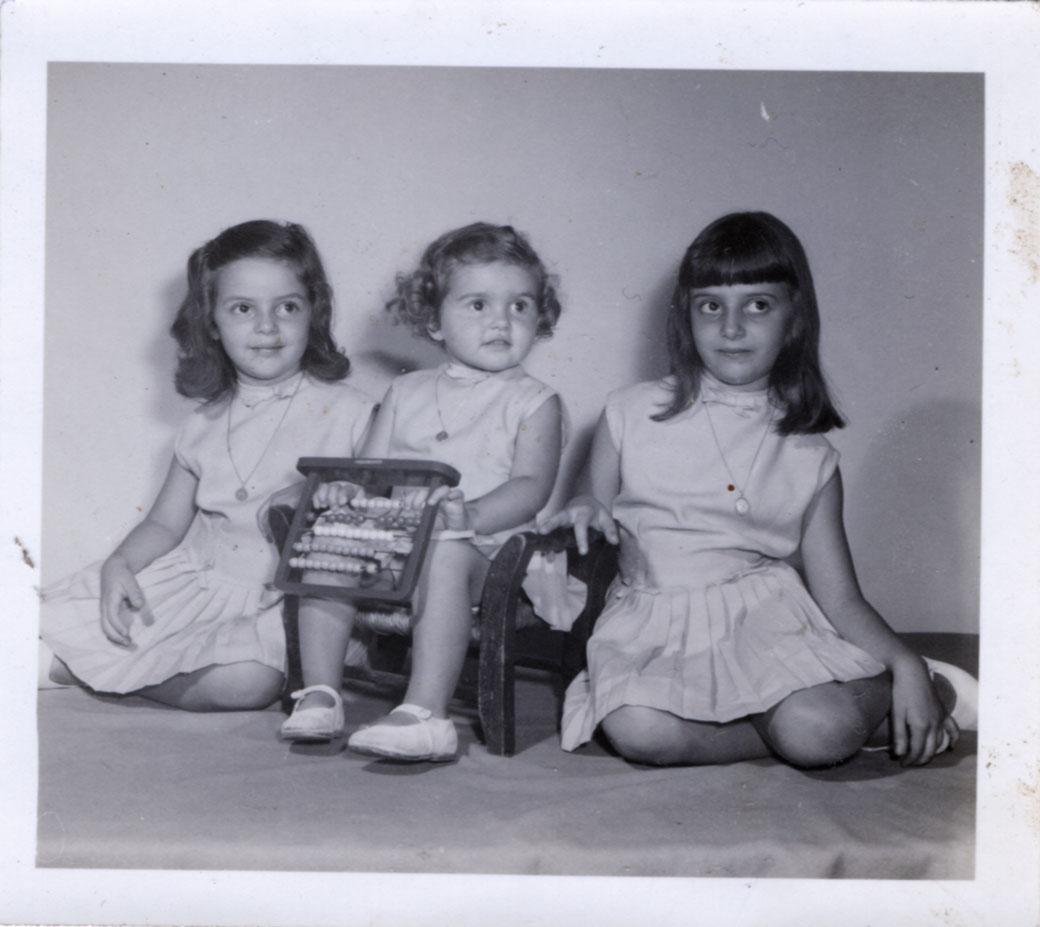 Mis hermanas y yo, vestidas iguales, es una foto en un estudio fotográfico, firmada con lápiz. No llego a identificar el nombre del fotógrafo.