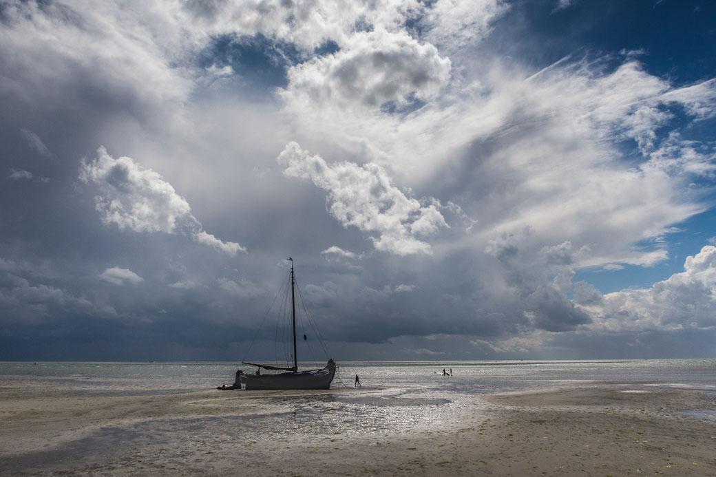 Drooggevallen zeilschip met op achtergrond een dreigende wolkenlucht boven de Noordsvaarder Terschelling