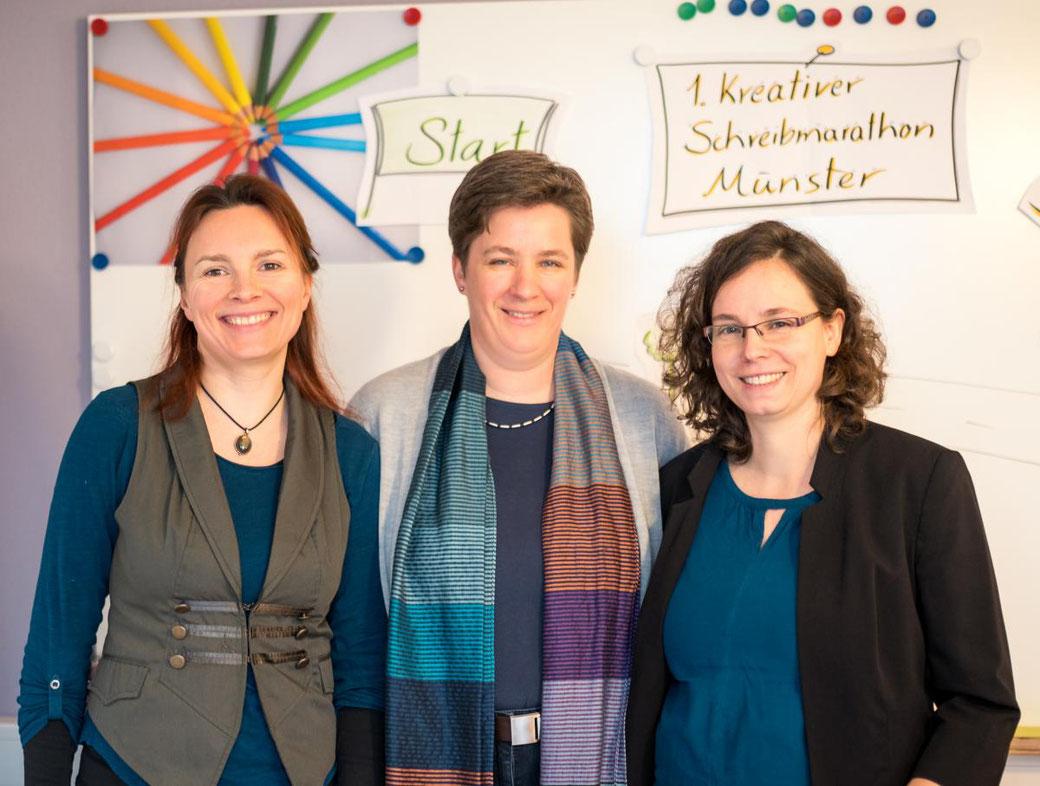 Drei Frauen stehen vor einem Whiteboard und lächeln in die Kamera.