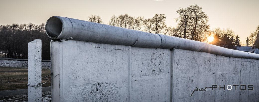 Ein Teil der DDR-Grenzmauer im Gegenlicht der Abendsonne der Aussenanlage des deutsch-deutschen Museums in Mödlareuth