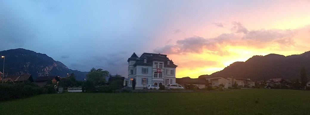 Adventure hostel Interlaken with the sun setting behind the Niederhorn