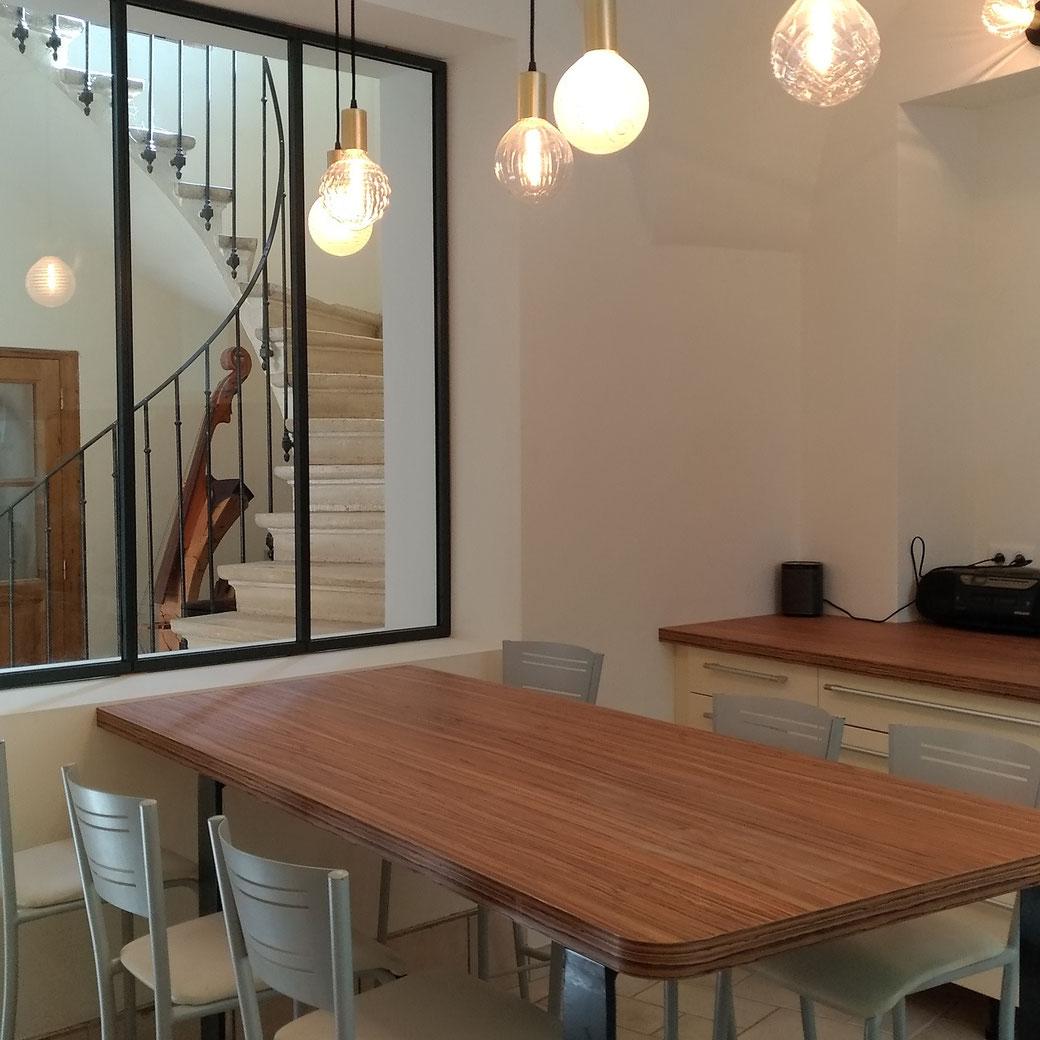 Cuisine avec plan de travail effet noyer et façades laquées écru, des rangements astucieux et des suspensions lumineuses en verre soufflé.
