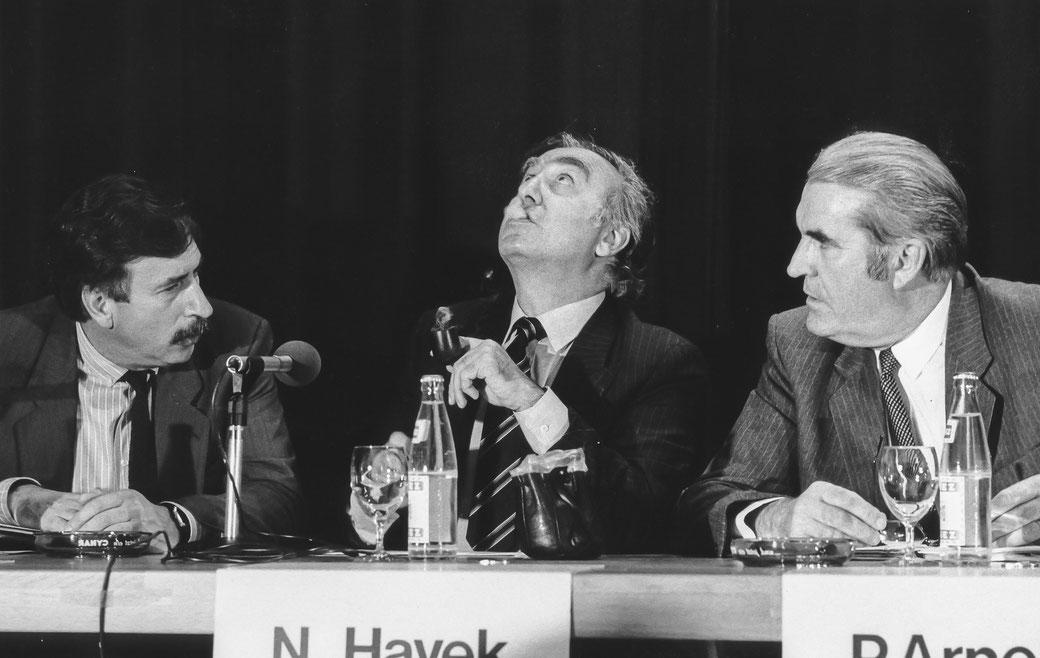 13.05.1985 / Nicolas G. Hayek bläst den Pfeiffenrauch - anlässlässlich der Pressekonferenz der Asuag und SSIH in Biel - nach oben, aufgenommen am 13. Mai 1985. Links Ernst Thomke und ganz rechts Pierre Arnold.  © Bild: Alain D. Boillat/Keystone