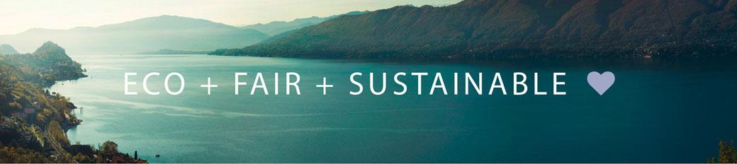 Text Eco + Fair + Sustainable mit Landschaftshintergrund