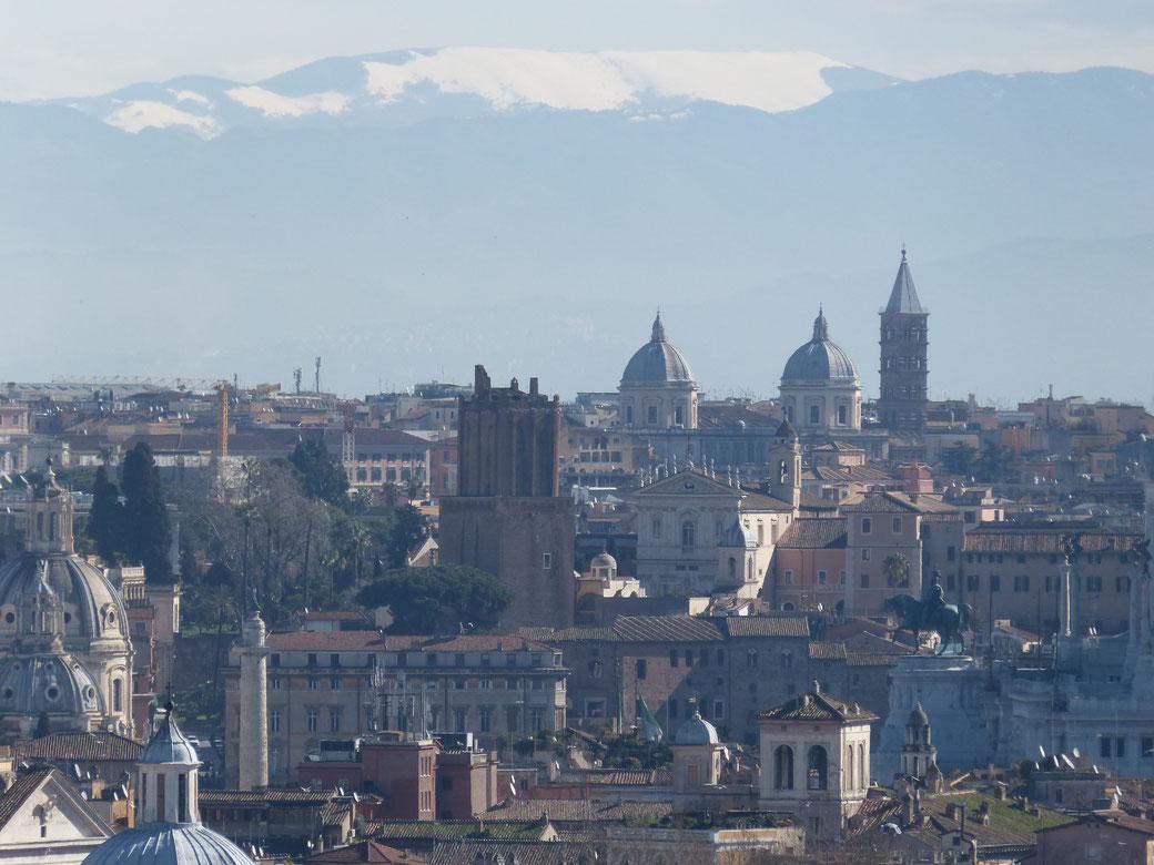 Aussicht vom Gianicolo auf schneebedeckte Berggipfel und das Dächermeer von Rom.