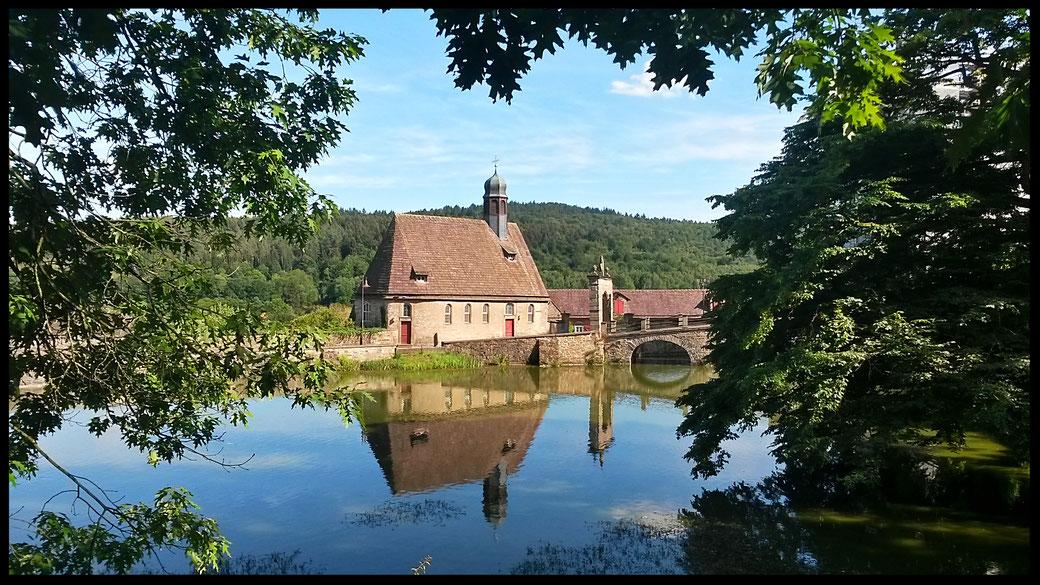 Die protestantische Kirche aus dem 16. Jahrhundert spiegelt sich romantisch  im Schlossweiher der Hämelschenburg