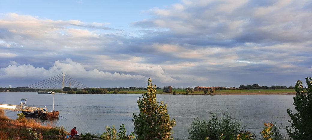 Abendlicher Blick auf den Schiffsanleger, die Autobrücke und die ehemalige Eisenbahnbrücke von der Rheinpromenade