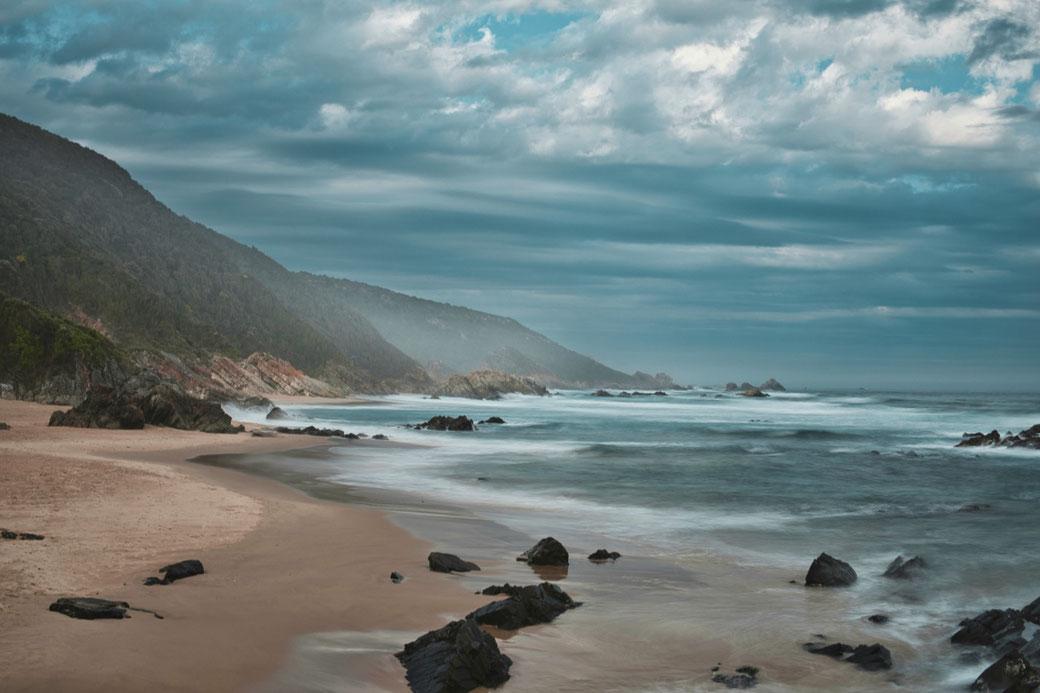 Das Meer flutet den Strand, im Hintergrund werden die Berge von der Gischt in Nebel getaucht