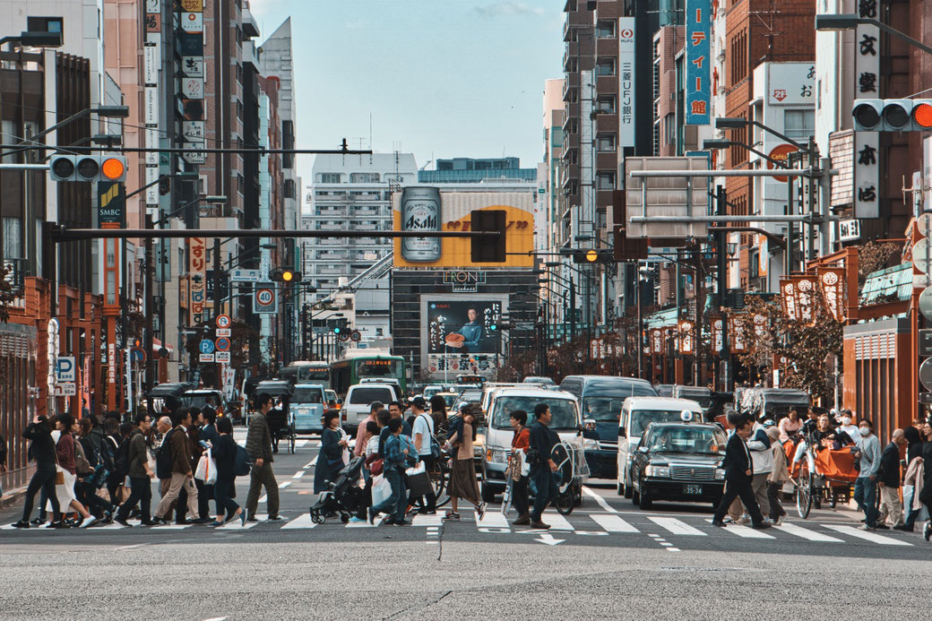 Strassenübergang in Tokio. Es strömen Menschen über die befahrene Kreuzung von links nach rechts