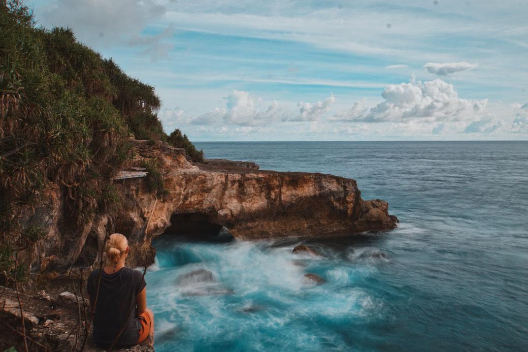 Steffi sitzt an Klippen und schaut aufs Meer