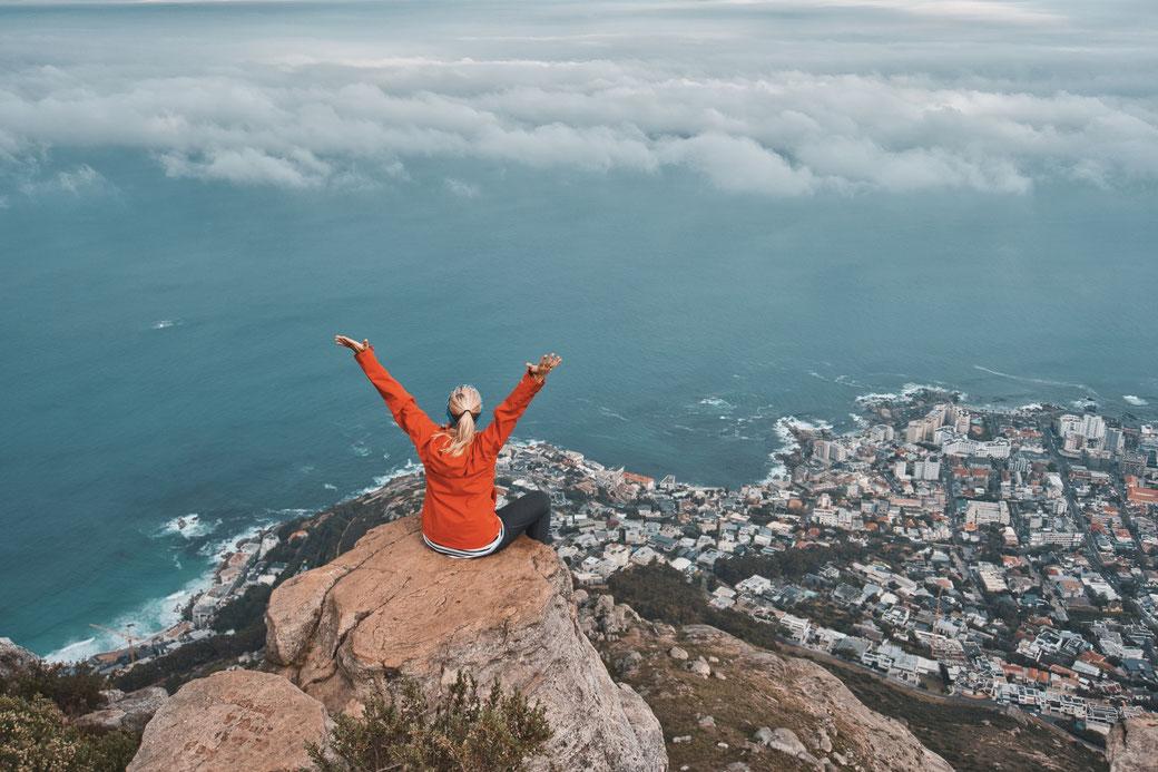 Frau sitzt auf einem Stein am Gipfel des Lion Heads. Unter ihr Kapstadt!