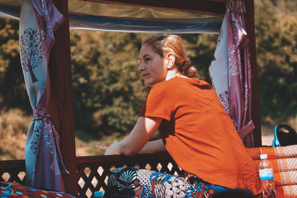 Frau schaut vom Slowboot auf den Mekong