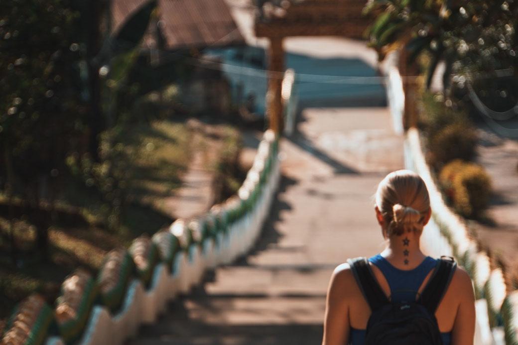 Frau läuft Treppe in Laos von einem Tempel runter