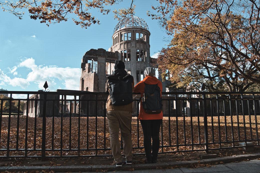 A Bomb Dome in Hiroshima. zwei Menschen stehen im vordergrund und schauen ihn an