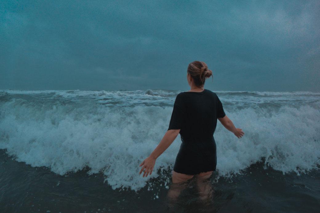 Frau im T-Shirt steht im Meer, während eine Welle auf sie zu rollt