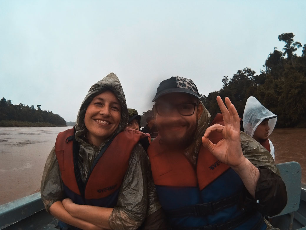 2 Menschen auf einem Fluss mit Regencapes. Kletschnass