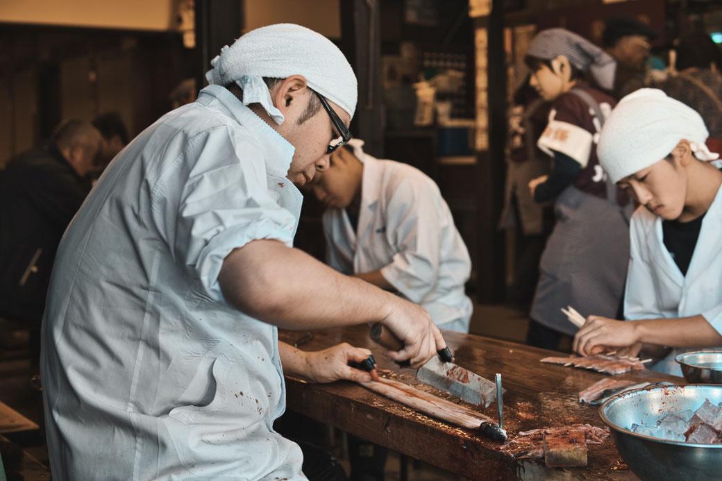 Zwei Japaner sitzen an einem Holztisch und zerlegen Aal mit einem Messer