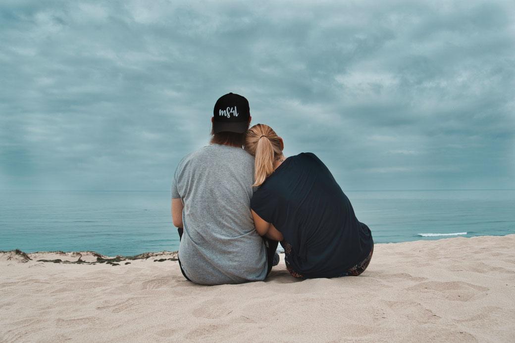 Steffi und Daniel sitzen auf einer Sanddühne und schauen ins Meer