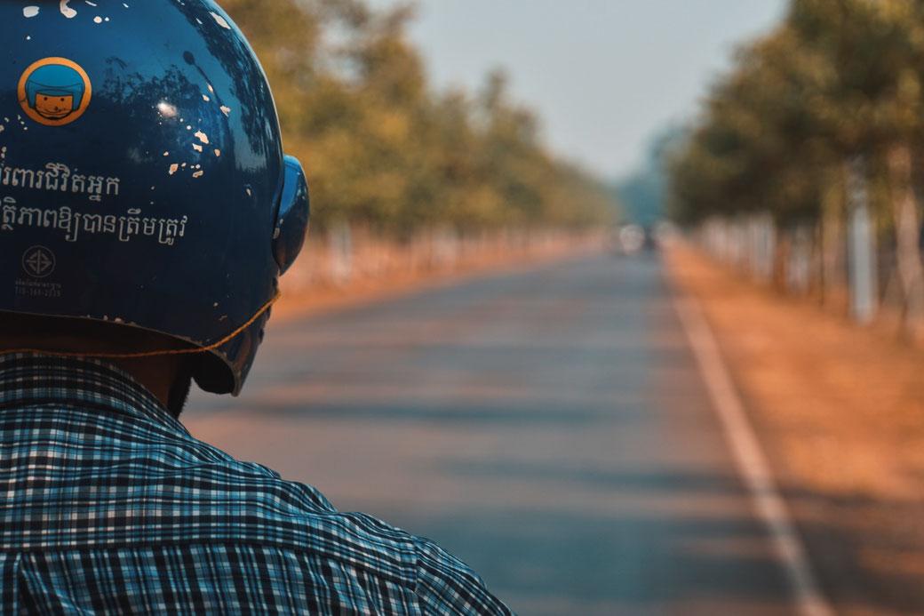 Mann auf Tuk Tuk auf staubiger Straße in Kambodscha