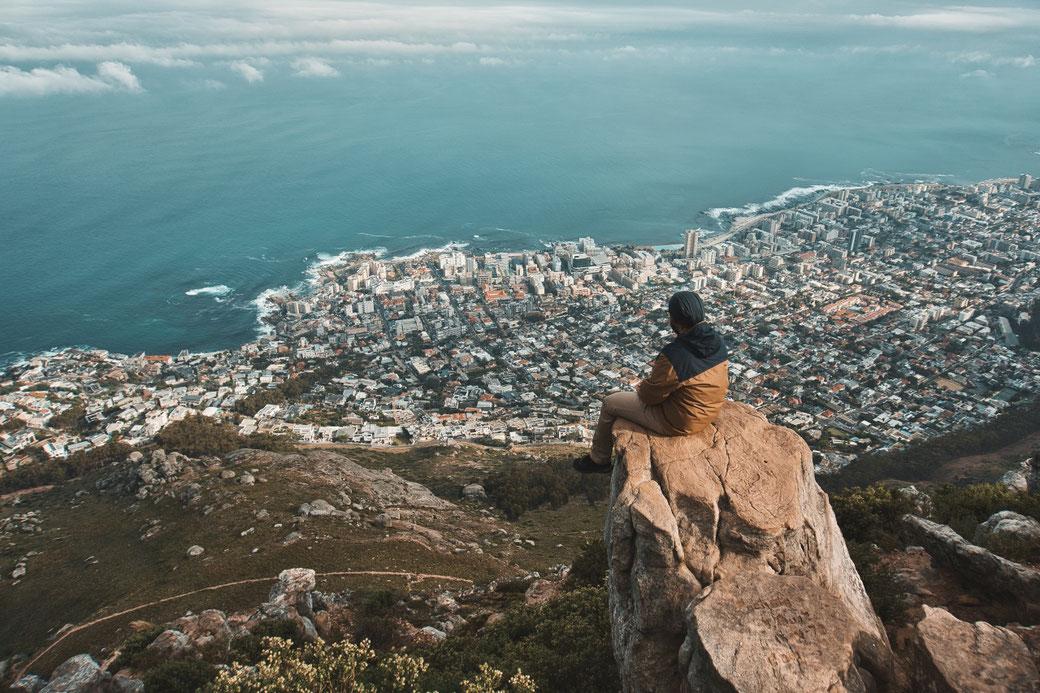 Mann sitzt am Abgrund auf einem Felsen des Lion Head und schaut auf Kapstadt