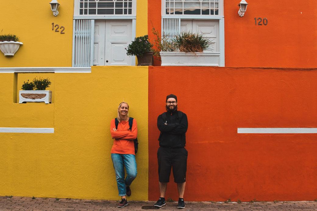 2 Menschen vor einer Häuserwand. die eine hälfte Orange, die andere hälfte gelb. Er hat shwarze sachen an. sie einen roten Pullover